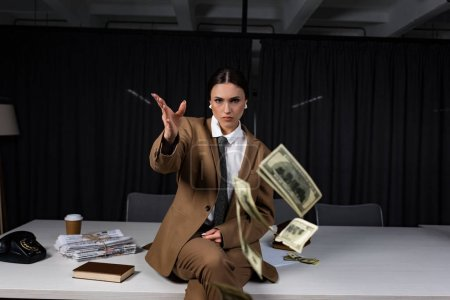 Photo for Businesswoman sitting on table, throwing money and looking at camera - Royalty Free Image