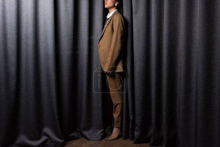 Foto de Vista lateral del modelo de moda en traje de pie en estudio con fondo de cortina gris - Imagen libre de derechos