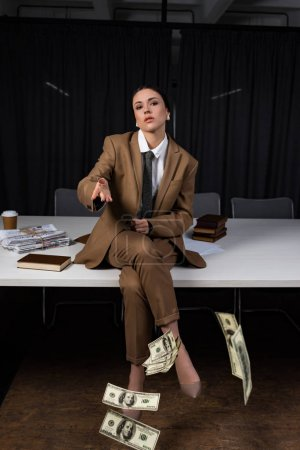 Photo for Adult businesswoman sitting on table, crossing legs, looking at camera and throwing money - Royalty Free Image