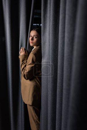Photo pour Vue latérale de la femme réussie en costume debout sur fond de rideau gris foncé, en regardant la caméra - image libre de droit