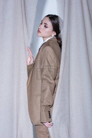 Foto de Vista lateral de la mujer de moda en traje de pie sobre el fondo de cortina gris claro - Imagen libre de derechos