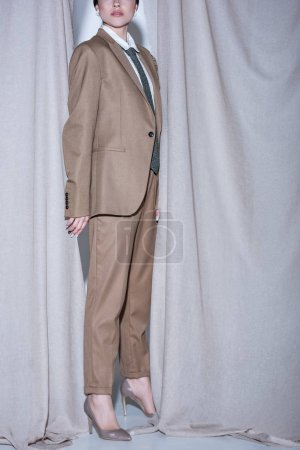 Foto de Vista recortada de la mujer exitosa en traje beige de pie sobre el fondo de cortina gris claro - Imagen libre de derechos