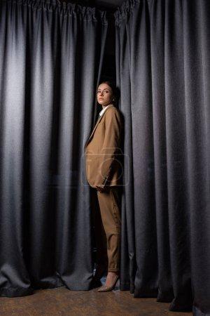 Foto de Vista lateral del modelo de moda en traje de pie sobre el fondo de cortina gris oscuro, mirando a la cámara - Imagen libre de derechos