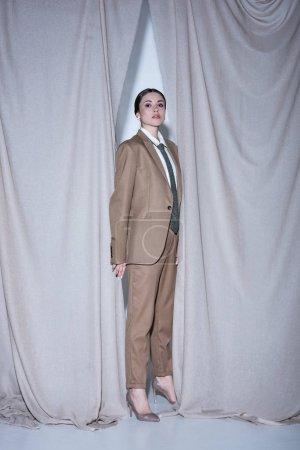 Foto de Modelo adulto en traje de pie sobre el fondo de cortina gris claro, mirando a la cámara - Imagen libre de derechos