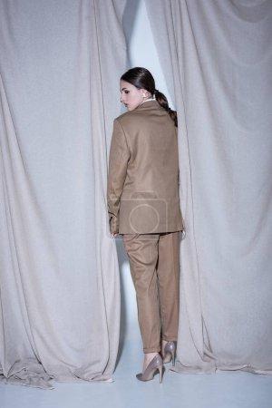 Foto de Vista trasera del modelo de moda en traje de pie sobre el fondo de cortina gris claro - Imagen libre de derechos