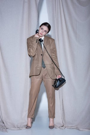 Foto de Mujer exitosa en traje de pie sobre el fondo de cortina gris claro, mirando hacia otro lado, hablando por teléfono - Imagen libre de derechos