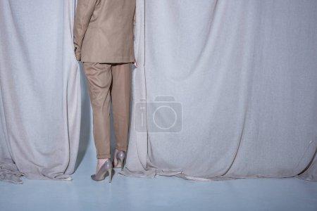 Foto de Vista recortada de la mujer de moda en traje de pie sobre el fondo de cortina gris claro - Imagen libre de derechos