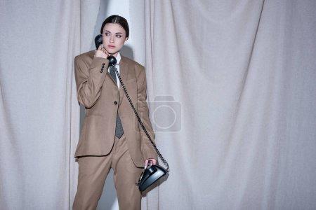 Foto de Modelo adulto en traje de pie sobre el fondo de cortina gris claro, mirando hacia otro lado, hablando por teléfono - Imagen libre de derechos