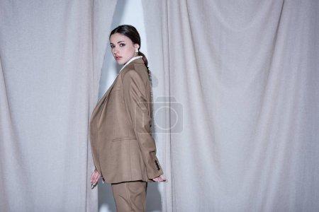 Foto de Vista lateral de la mujer exitosa en traje de pie sobre el fondo de cortina gris claro, mirando a la cámara - Imagen libre de derechos