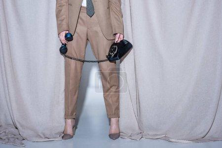 Foto de Vista recortada del modelo de pie sobre el fondo de la cortina gris claro y el teléfono del teléfono en la mano - Imagen libre de derechos