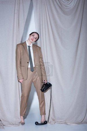 Foto de Mujer de moda en traje beige de pie sobre el fondo de la cortina y la celebración del teléfono - Imagen libre de derechos