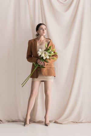 Foto de Modelo de moda en vestido beige y blazer de pie sobre fondo cortina con flores - Imagen libre de derechos