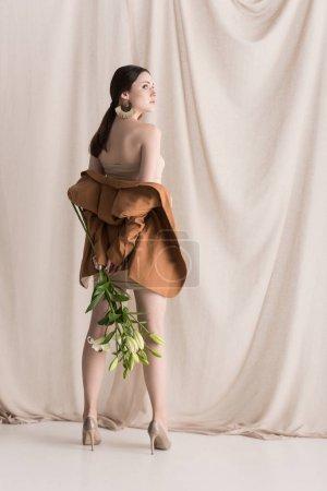 Foto de Modelo de moda de pie sobre el fondo cortina, sosteniendo las flores en las manos - Imagen libre de derechos