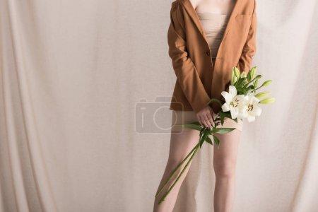 Foto de Vista recortada de la mujer sosteniendo flores en las manos, de pie sobre el fondo de la cortina - Imagen libre de derechos