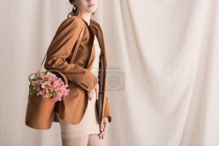 Foto de Vista recortada de la mujer con estilo lleva flores en bolsa, de pie sobre el fondo de la cortina - Imagen libre de derechos