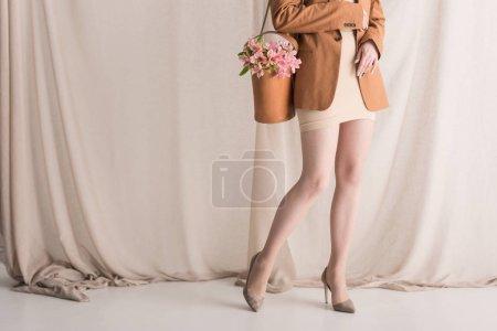 Foto de Vista recortada del modelo en ropa de moda lleva flores en el bolso de hombro, de pie sobre el fondo de la cortina - Imagen libre de derechos