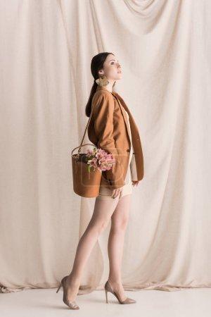 Foto de Lado veiw de la mujer de moda lleva flores en bolsa, de pie sobre el fondo de la cortina - Imagen libre de derechos