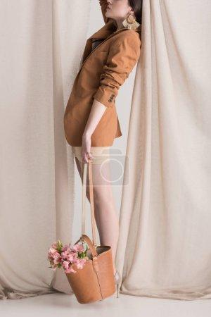 Foto de Vista lateral de la hermosa mujer en vestido beige llevando flores en bolsa con cortina en el fondo - Imagen libre de derechos