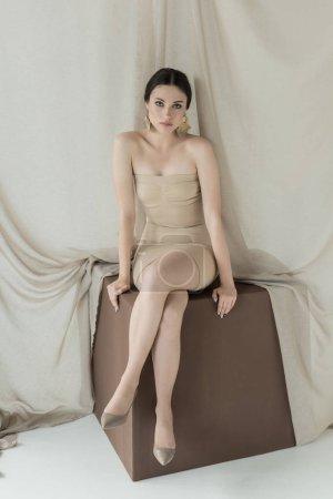 Foto de Mujer de moda en el vestido sentado en cubo con fondo de cortina de luz, mirando a la cámara - Imagen libre de derechos