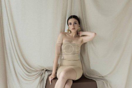 Photo pour Belle femme dans la robe s'asseyant sur le cube avec le fond léger de rideau, cou touchant, regardant l'appareil-photo - image libre de droit