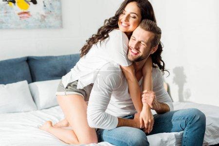 Photo pour Heureux sourire couple étreignant dans le lit le matin - image libre de droit