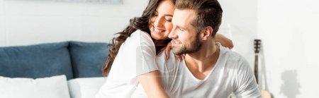 Photo pour Plan panoramique de femme souriante heureuse embrassant l'homme au lit le matin - image libre de droit