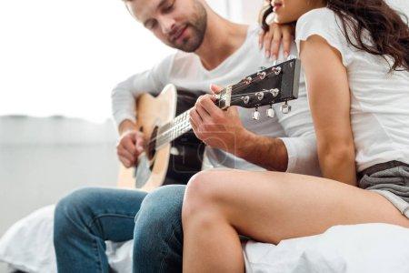 Photo pour Foyer sélectif de l'homme jouant la guitare acoustique près de la femme - image libre de droit
