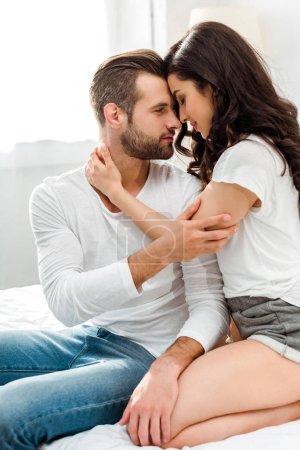 Photo pour Couple romantique embrassant doucement et se regardant dans le lit - image libre de droit