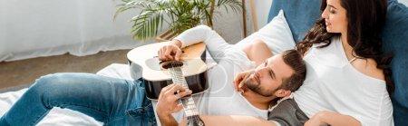 Photo pour Plan panoramique de l'homme couché avec guitare acoustique près de la femme au lit - image libre de droit