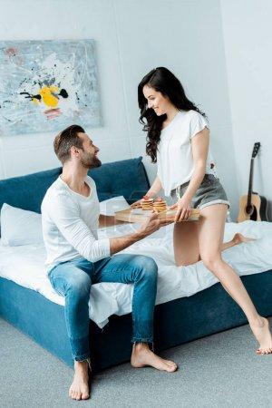 beautiful woman giving tray with breakfast to boyfriend in bedroom