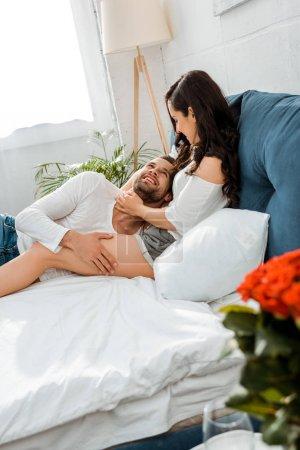 Photo pour Belle jeune couple heureux couché et câlin au lit - image libre de droit