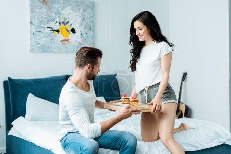 Photo pour Petite amie heureuse donnant plateau avec crêpes au petit ami dans la chambre - image libre de droit