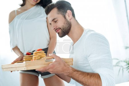 Photo for Handsome man holding wooden tray with tasty pancakes - Royalty Free Image