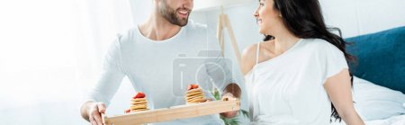 Photo for Panoramic shot of smiling man holding wooden tray with tasty pancakes near girlfriend - Royalty Free Image