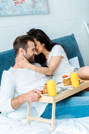 Photo pour Femme embrassant doucement l'homme avec le petit déjeuner sur un plateau en bois au lit - image libre de droit