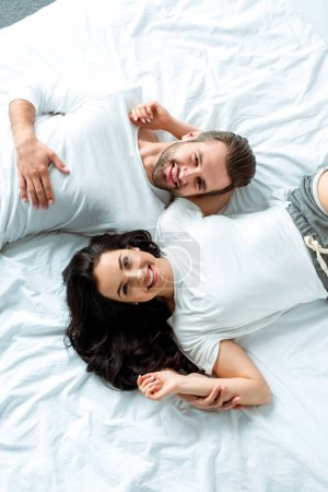 Photo pour Top view of happy couple lying together in bed - image libre de droit