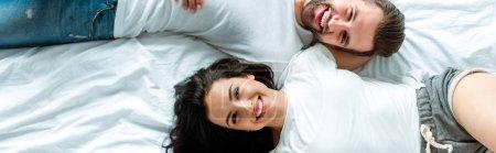 Photo pour Vue supérieure du couple heureux se trouvant ensemble dans le lit, projectile panoramique - image libre de droit