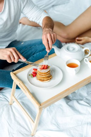 Photo for Cropped view of man eating pancakes with strawberries and drinking tea in bed - Royalty Free Image