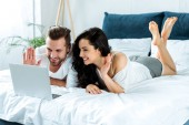 """Постер, картина, фотообои """"happy couple waving hands during video chat on laptop and lying in bed, illustrative editorial"""""""