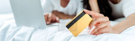 Photo for Selective focus of woman holding credit card near man with laptop, panoramic shot - Royalty Free Image