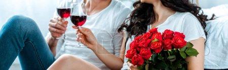 Photo pour Vue recadrée du couple cliquetant avec des verres de vin rouge et tenant des roses rouges, prise de vue panoramique - image libre de droit