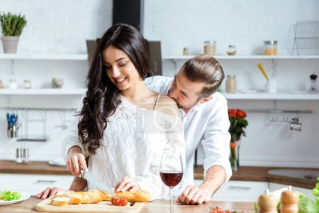 handsome man cutting bread on chopping board and kissing girlfriend shoulder