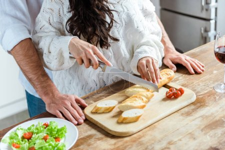 Photo for Cropped view of couple standing together at kitchen while woman cutting bread on chopping board near fresh salad - Royalty Free Image