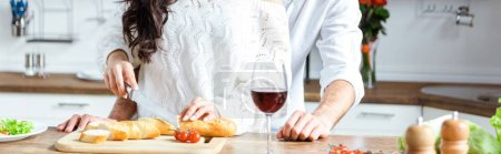 Photo for Cropped view of couple standing together at kitchen while woman cutting bread on chopping board, panoramic shot - Royalty Free Image