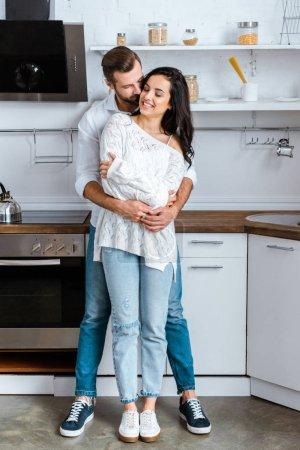 Photo pour Vue pleine longueur de l'homme embrassant doucement femme heureuse à la cuisine - image libre de droit