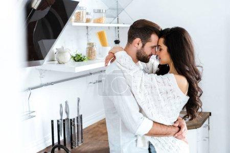 Photo pour Beau couple embrassant doucement avec les yeux fermés à la cuisine - image libre de droit