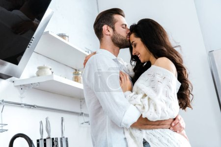 Photo for Man with closed eyes gently hugging and kissing woman - Royalty Free Image