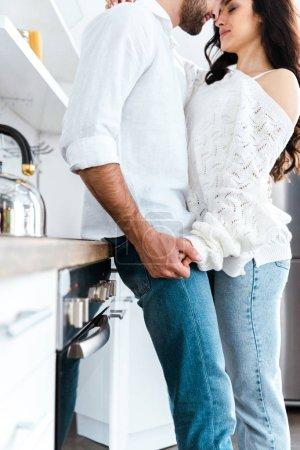 przycięte widok mężczyzny i kobiety delikatnie trzymając ręce w kuchni