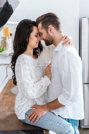 Photo pour Homme et femme embrassant doucement à la cuisine - image libre de droit