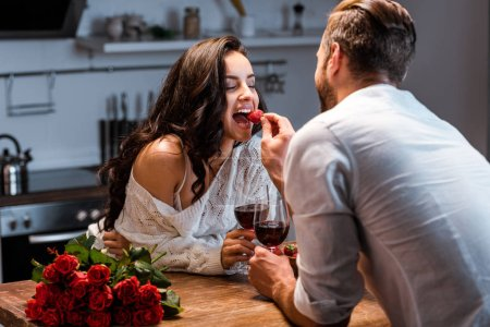 Photo for Couple with glasses of red wine at wooden table with bouquet of roses, man feeding woman with strawberry - Royalty Free Image
